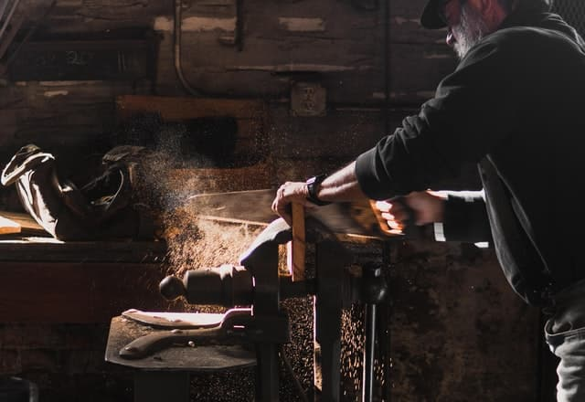 Man doing woodworking with a saw