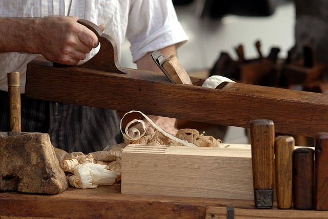 carpenter touching wood with shavings underneath