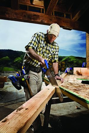 Man cutting wood with IRWIN tools universal handsaw