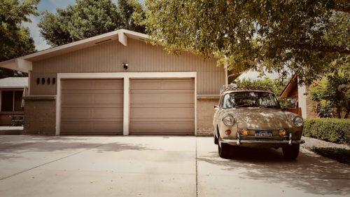 a white car parked outside a garage