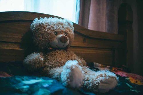 bear leaning on headboard