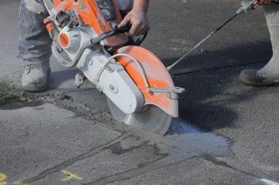 man operating a circular saw to cut through concrete