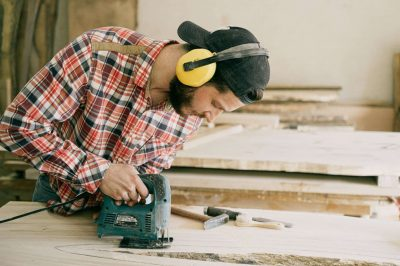 man with green power tool