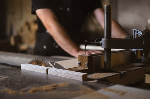 hands cutting wood and table saw fence