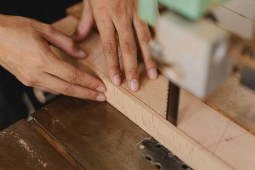 man cutting wood with bandsaw
