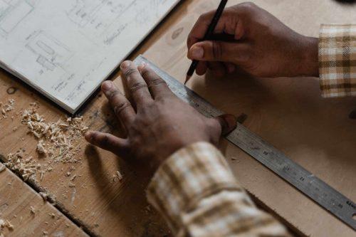 hands marking measurements on wooden board