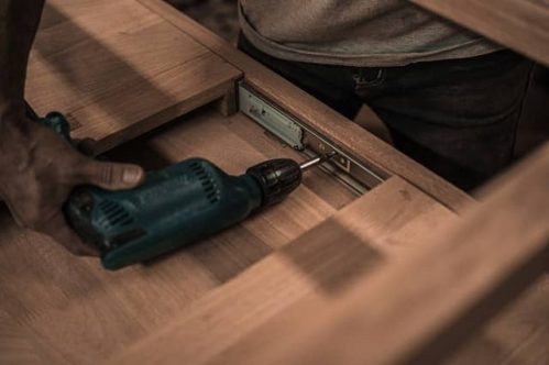 man using hand drill