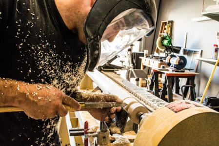 man with shield doing woodwork